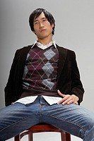 Fashionable young man sitting on chair (thumbnail)