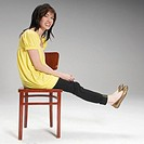 Playful young woman sitting on a chair (thumbnail)