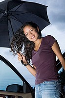 Young woman getting out of a car with an umbrella