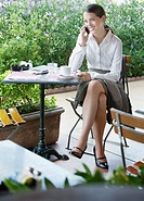 Businesswoman on outdoor patio with her mobile phone