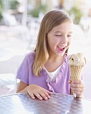 Young girl on outdoor patio with ice cream cone