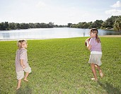 Two young kids outdoors at park playing with a football by a lake