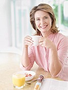 Woman in kitchen eating breakfast