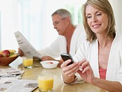 Couple in kitchen eating breakfast and reading newspaper