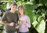 Couple outdoors by trees holding mugs