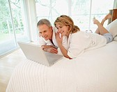 Couple in bed using laptop