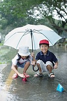 Two young kids outdoors in rain playing with paper boats (thumbnail)