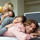 Family in living room lying on top of each other