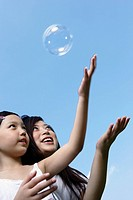 Woman and young girl outdoors playing with bubble
