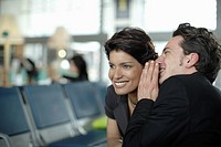 Man in airport whispering in woman´s ear