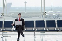Businessman in airport with laptop and mobile phone. Barcelona El Prat Airport. Spain
