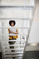 Businesswoman on office space holding folder at bottom of staircase