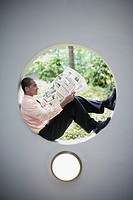 Businessman sitting in round window reading newspaper