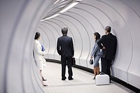 Five businesspeople standing in corridor waiting