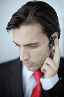 Businessman indoors wearing earpiece