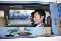 Two businesspeople in car with coffee cups