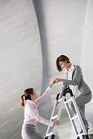Two businesswomen in structure on ladder