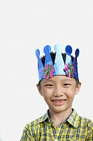 Young boy indoors wearing party hat smiling