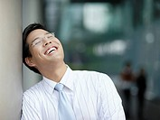 Businessman outdoors laughing leaning against large pillar