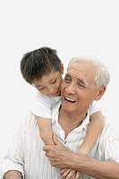 Young boy indoors with arms around man