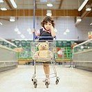 Young girl in grocery store with shopping cart