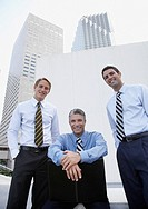 Three businessmen outdoors with a chair