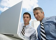 Two businessmen outdoors with a laptop