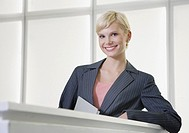 Businesswoman standing in office looking at camera