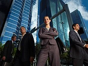 Businesswoman outdoors looking at camera with three businesspeople around her