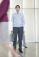 Businessman in office holding bag with co-workers going by