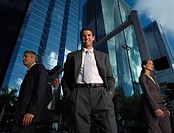 Businessman outdoors looking at camera with three businesspeople around him