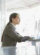 Businesswoman on outdoor patio with laptop