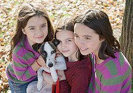 Three young girls outdoors with a dog