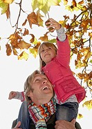 Man holding up young girl to pick something off a tree