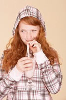 Young girl indoors drinking strawberry milkshake