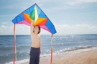 Young boy at the beach holding a kite