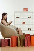 Woman sitting in department store using her mobile phone