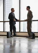 Two businessmen in corridor by large windows