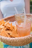 Woman serving basket of iced tea and tortilla chips