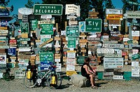 Biker, in, front, of, Sign, post, forest, Watson, Lake, Yukon, Canada