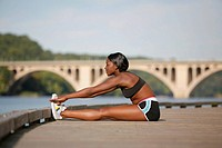 Woman doing exercises beside river