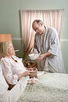 Man offering soup to sick woman in bed