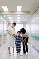 Boy 5-6 with mother and nurse in hospital corridor