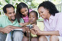 Boy and a girl looking at a digital camera with their parents