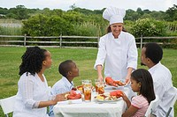 Female chef serving food to a family seated at the breakfast table in a park