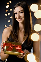 Young woman holding wrapped gift, portrait