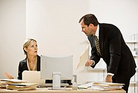 Businessman scolding businesswoman at desk with piles of paperwork