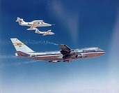 In this 1974 NASA Flight Research Center FRC photograph, the two chase aircraft, a Learjet and a Cessna T_37, are shown in formation off the right win...