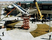 While workers on the ground steady the craft with guy ropes, workers atop a high_lift truck align the mounting plates as an F/A_18 Hornet airplane for...