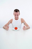 man with tomato at plate